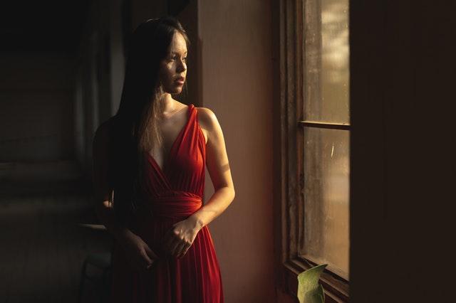 Dívka v červených společenských šatech stojící u okna